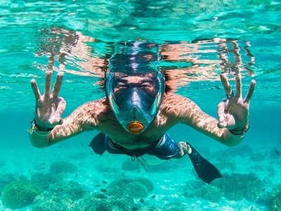 man with full face snorkel mask underwater
